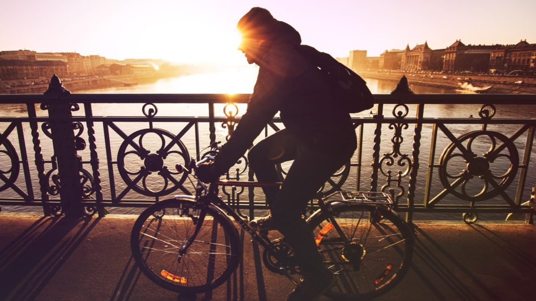 Woman cycling while the sun rises