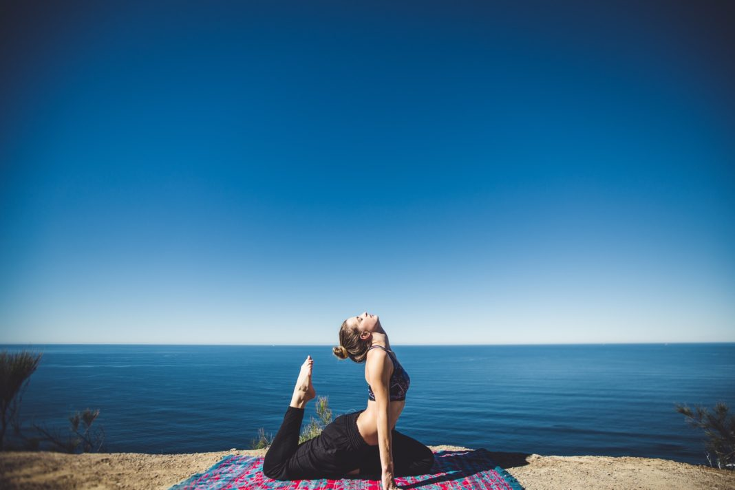 Woman doing yoga by the sea side