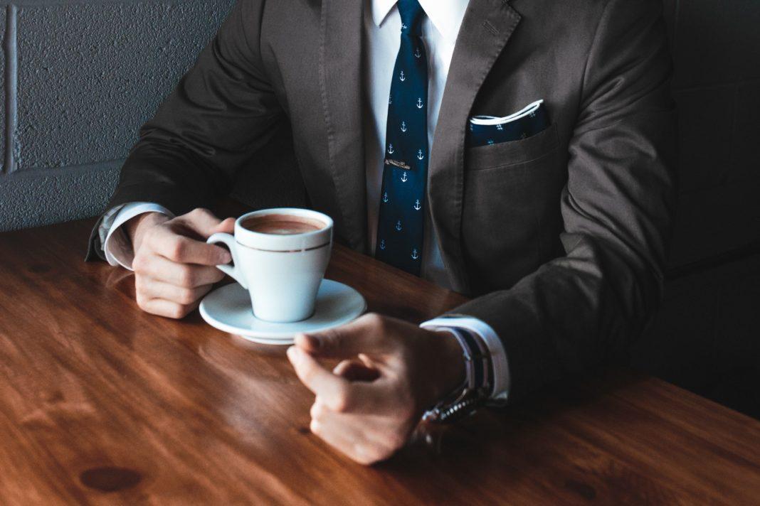 Man in a tuxedo, drinking coffee